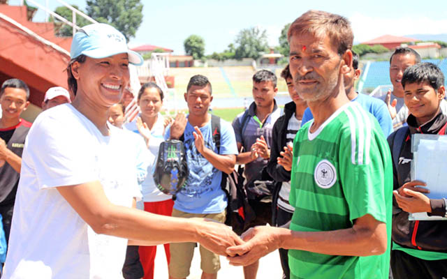 Manita Sahi (left) national taekowndo player handovers financial support for medical treatment to Madhu Nepali former Lawn Tennis ball boy who is suffering from lung illness fcollected from national players in camp training at the Dasharath Stadium in Kathmandu on Tuesday. Photo: THT