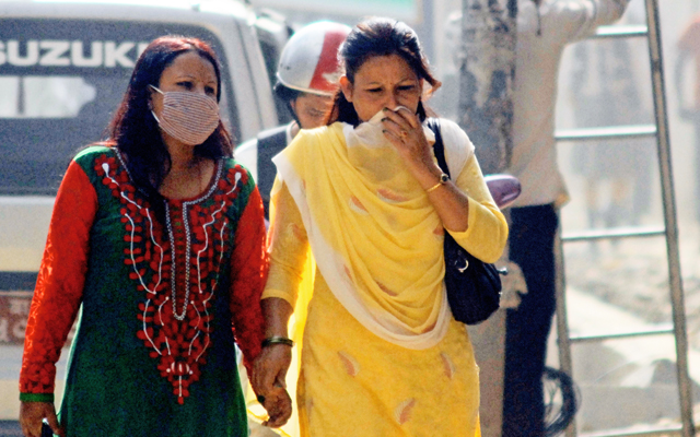 A woman uses facemask while her friend covers her nose with a shawl to avoid dust, in Bagbazaar, Kathmandu, on Thursday. Photo: THT