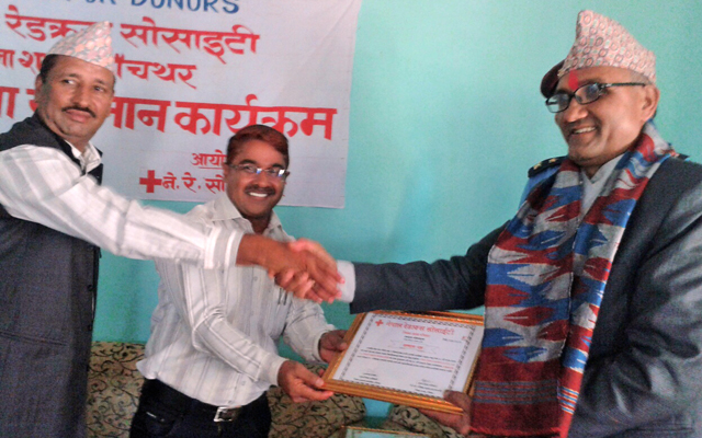 Panchthar CDO Purushottam Ghimire (centre) felicitating Dina Nath Ghimire (right), who has donated blood 68 times, on the premises of Nepal Red Cross Society District Chapter Office. Photo: THT