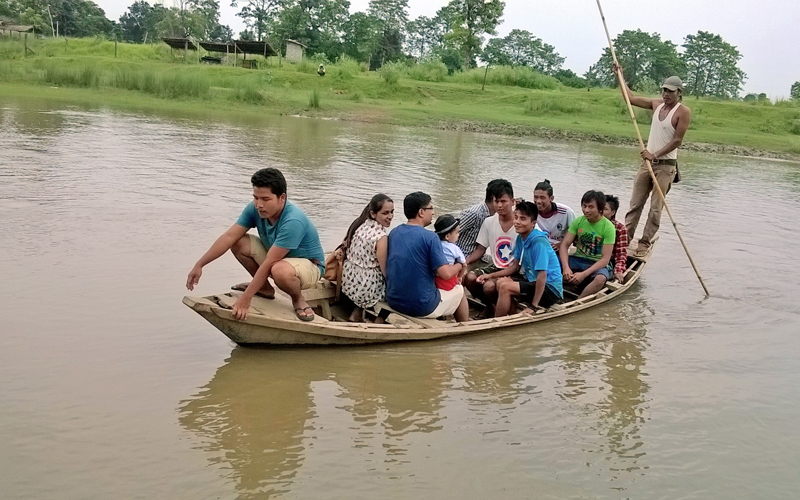 Domestic tourists enjoying a boat ride as they cross the Budhi Rapti River in the Chitwan National Park, Sauraha on Thursday, July 23, 2015. Photo: Tilak Ram Rimal