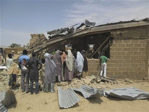 People gather at the site of suicide bomb attack at Redeem Christian church in Potiskum, Nigeria, Sunday, July 5, 2015. Witnesses say a woman suicide bomber blew up in the midst of a crowded evangelical Christian church service on Sunday and killed at least five people, the latest in a string of bombings and shooting attacks blamed on the Islamic extremist group Boko Haram that has killed some 200 people in the past week. Photo: Ap
