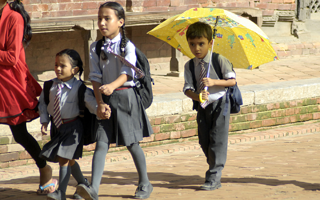 A boy using an umbrella as he returns from school with his friends, in Patan Durbar Square, Lalitpur, on Thursday. A day after rains lashed Kathmandu; temperature in the capital city rose to 29.5 degrees Celsius. Photo: Photos: Naresh Shrestha/ THT