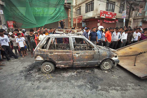 Bystanders looking at the charred remains of a taxi, which was set alight during a general strike, being towed on to the back of a truck in Naya Bazaar, Kathmandu, on Friday. Photo :THT