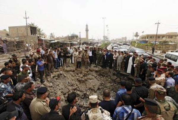 Residents and Iraqi security forces gathering around a hole caused by a suicide car attack at a market in Khan Bani Saad, northeast of Baghdad, on Saturday. Photo:Reuters