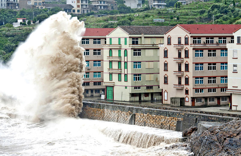 A wave, under the influence of Typhoon Chan-hom, hitting the shore next to residential buildings in Wenling, Zhejiang province, China, on Saturday.  Photo: AP
