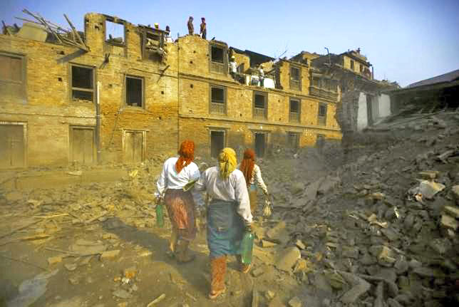 Women walk past collapsed houses as the wreckage is manually demolished following the April 25 earthquake in Bhaktapur, Nepal, June 5, 2015. Reuters