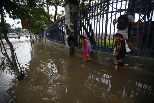 Pedestrians taking the support of a railing to cross a waterlogged footpath near Bhadrakali, Kathmandu,  on Wednesday. PHOTO:SKANDA GAUTAM/THT