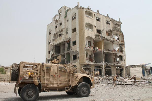 Yemeni fighters loyal to exiled President Abedrabbo Mansour Hadi stand in front of a damaged building in Aden's Khormaksar district on July 15, 2015. Photo: AFP