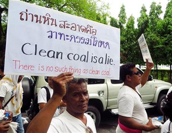 In this Monday July 20, 2015 photo, a protester holds a placard outside the Prime Minister's office in Bangkok during a demonstration opposing a proposed coal power plant in southern Thailand. The popular tourist beaches near southern Thailand's Andaman Coast may soon play host to an unlikely new fixture: an 800-megawatt coal power plant. The plans have sparked an outcry in the typically tranquil Krabi province, famed for its white sand and picturesque limestone cliffs. Photo: AP