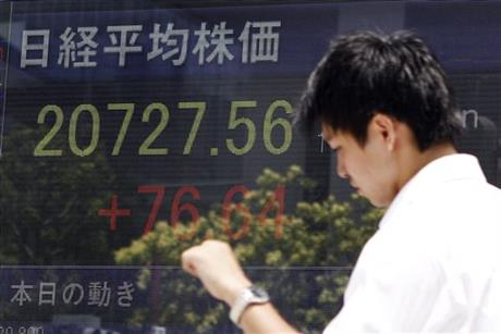 A businessman walks by an electronic board displaying Japan's Nikkei 225 index in Tokyo, Tuesday, July 21, 2015. Most Asian stock markets were modestly higher Tuesday after positive US earnings reports boosted sentiment. AP