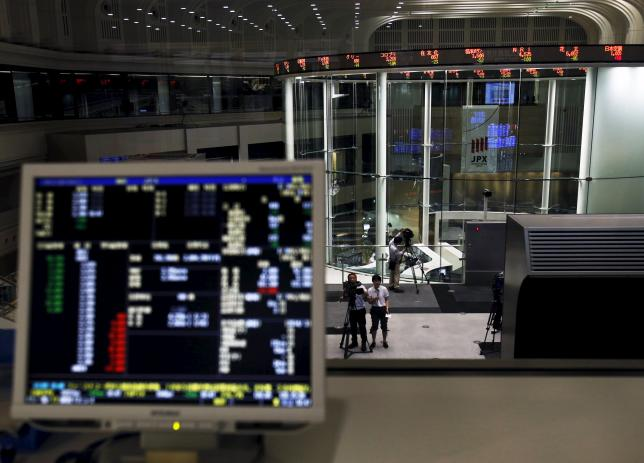 A videographer films an electronic board showing the Japan's Nikkei average and related indexes is seen next to a computer showing the market indexes at the Tokyo Stock Exchange (TSE) in Tokyo, Japan, July 9, 2015. REUTERS/Yuya Shino