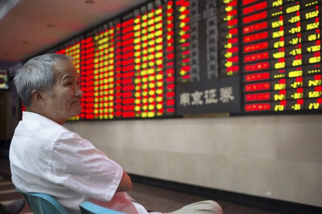 An investor looks at an electronic board showing stock information at a brokerage house in Nanjing, Jiangsu province, China, July 30, 2015. REUTERS/China Daily