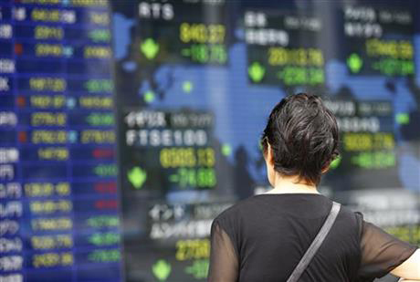 A woman looks at an electronic stock indicator of a securities firm in Tokyo, Tuesday, July 28, 2015. Photo: AP