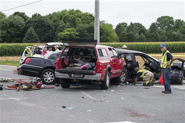 Authorities investigate the scene of a fatal crash between a limousine and sports utility vehicle Saturday, July 18, 2015, in Cutchogue, N.Y. Multiple visitors to New York wine country were killed Saturday and others were seriously injured in the crash on the eastern end of Long Island, law enforcement officials said. Photo: Ap
