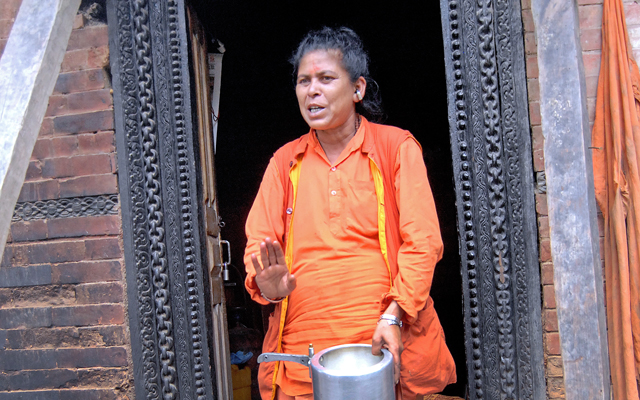 A female sadhu walking out of her abode with an empty cooking vessel near Pashupatinath Temple, in Kathmandu, on Thursday. Photo: THT