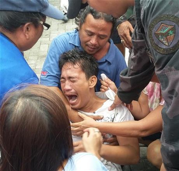 Police and rescuers comfort a crying passenger after he was brought ashore from a capsized passenger ferry Thursday, July 2, 2015, in Ormoc city, central Philippines. Coast Guard officials say the boat capsized minutes as it left a central Philippine port in choppy waters, leaving dozens dead and many missing. Photo: AP