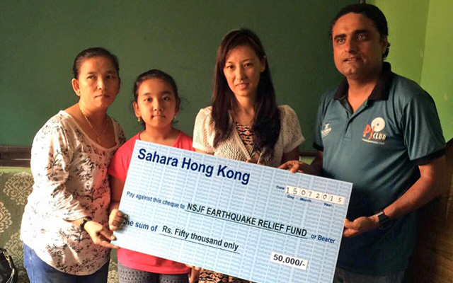 Sahara Club Hong Kong member Sarita Gurung handing over a cheque of Rs 50,000 to NSJF President Ajay Phuyal in Kathmandu on Wednesday. Sahara Hong Kong provided the financial help for family members of sports journalist Suman Bhomjan, who was killed in April 25 earthquake. Photo: THT