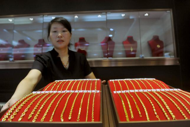 A sales woman displays a gold bracelets as she poses for pictures at a jewellery shop in Lin'an, Zhejiang province, China, July 29, 2015. REUTERS/China Daily