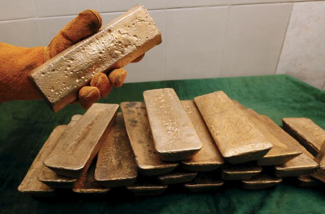 A melter places an ingot of 92.96 percent pure gold at a procession plant of the Olimpiada gold operation, owned by Polyus Gold International company, in Krasnoyarsk region, Eastern Siberia, Russia, June 30, 2015.  REUTERS/Ilya Naymushin