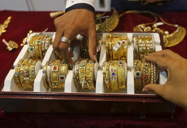 A salesman helps a customer (R) to select gold bangles at a jewelry showroom in Mumbai, May 21, 2015. REUTERS/Shailesh Andrade