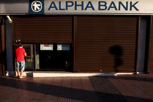 A man withdraws money at an Alpha Bank branch ATM in central Athens, Greece, July 19, 2015. Photo: REUTERS