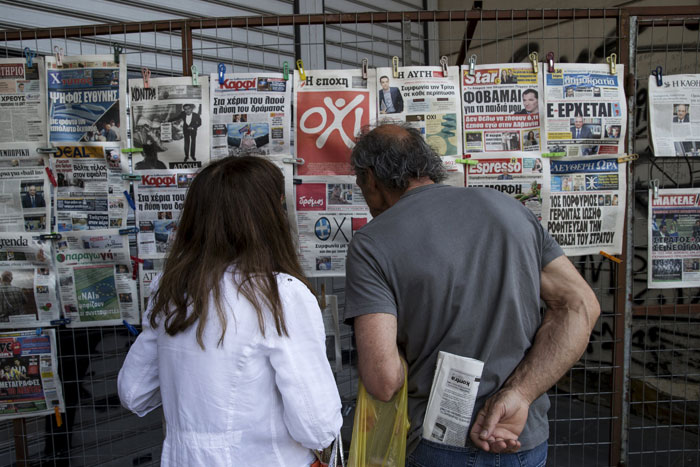 People read newspapers on a street in Athens, Greece, July 3, 2015. An opinion poll on Greece's bailout referendum published on Friday pointed to a slight lead for the Yes vote, on 44.8 percent, against 43.4 percent for the No vote that the leftwing government backs.  Photo: Reuters