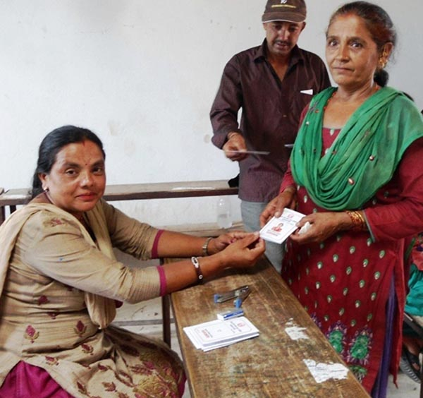 A staffer of Panchkhal Municipality handing over identity card to a tremor victim at the municipality in Kavre, on Wednesday.  nPhoto: THT