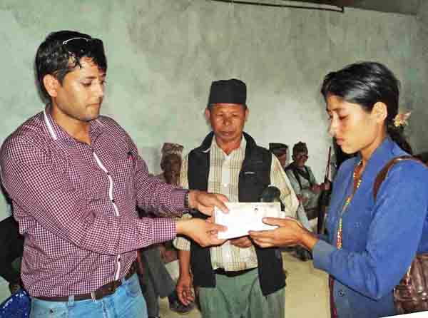 Diktel Municipality officer Narayan Dhakal handing over ID card to an earthquake victim along with nrelief amount to build shelter at a programme organised in the municipality office, in Khotang, on Sunday. Photo: THT