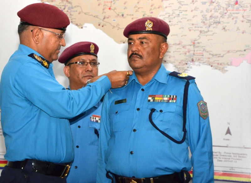 IGP Upendra Kant Aryal confers insignia on a newly promoted police official at a function in the Capital on Sunday, July 26, 2015. Photo: Nepal Police