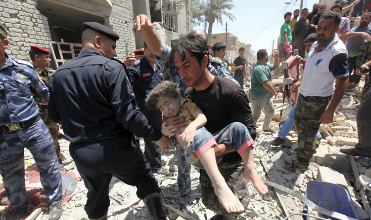 A man carrying an injured child found in the rubble after an Iraqi Sukhoi jet accidentally dropped a bomb in Ni'iriya district in Baghdad, on Monday. Photo: Reuters