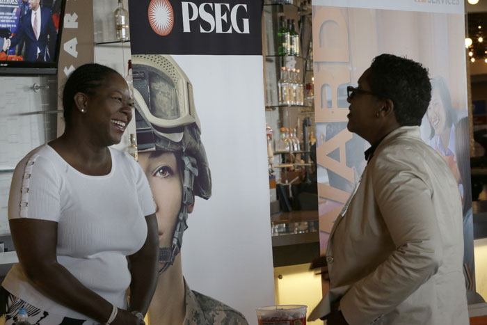 In this photo taken Tuesday, June 30, 2015, Sophia Lewis, left, with PSEG Long Island, speaks to an attendee about employment opportunities during a job fair at Citi Field in New York.  Photo: AP