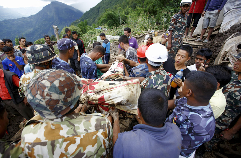 Rescue team members from Nepali Army retrieving the body of a landslide victim at Lumle village in Kaski district, on Thursday. Photo: Reuters