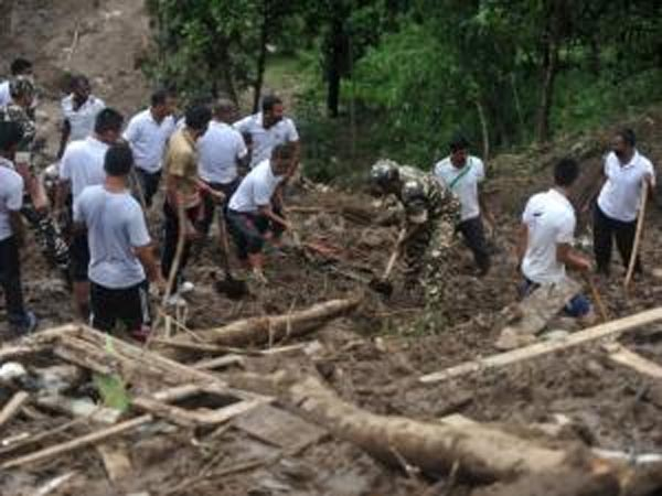 Indian rescue workers searching for bodies of those killed in a landslide at Tingling village near Mirik, some 60 km from Siliguri on Wednesday. Landslides triggered by heavy rain killed at least 21 people in the area. Photo: AFP