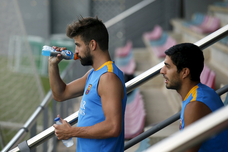 Barcelona's soccer players Gerard Pique (L) and Luis Suarez attend a training session at Joan Gamper training camp, near Barcelona, Spain, July 15, 2015. Photo: Reuters