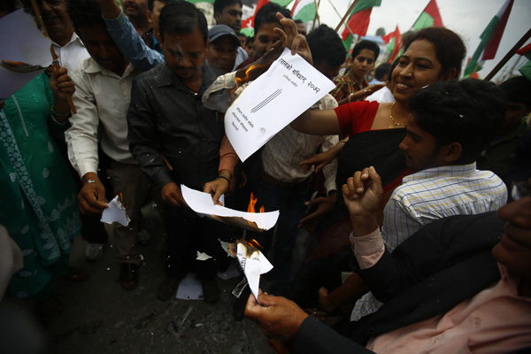 Members of Madhes-based parties burning copies of the draft constitution, which was submitted to CA on Tuesday, in Babarmahal, Kathmandu, on Wednesday.nPhoto: THT