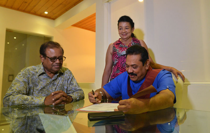 Former Sri Lankan leader Mahinda Rajapakse (R) signs nomination papers as party general secretary Susil Premajayantha (L) and his wife Shiranthi Rajapakse (C) look on at his home in a suburb of Colombo on July 9, 2015. Rajapakse secured nominations from his United People's Freedom Alliance to contest the forthcoming August parliamentary elections, clearing the way for a comeback months after being defeated at presidential polls in January 2015. Photo: AFP