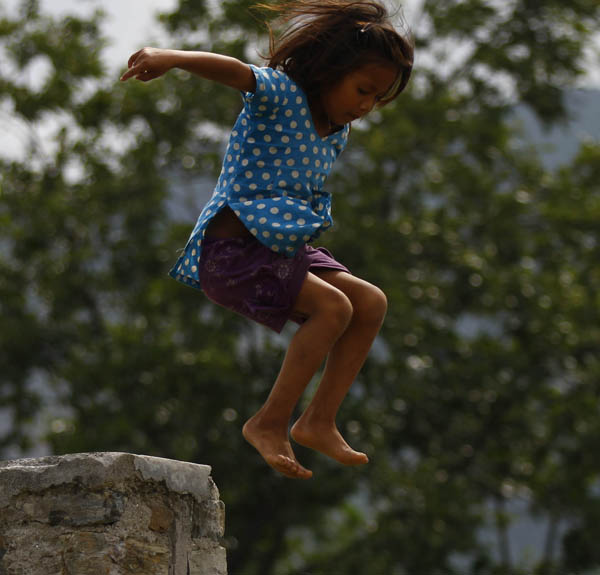 A child, who resides in a makeshift tent, playfully jumping off a dividing wall in Chasikot, Lalitpur, on Thursday. Photo:THT