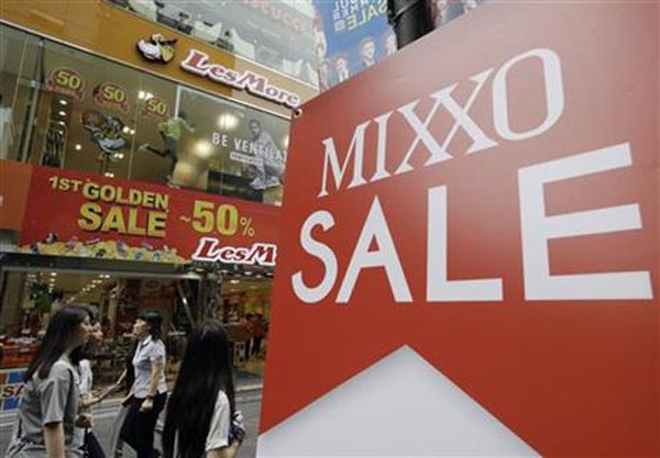 People walk past sale signs at a Seoul shopping district, South Korea, Thursday, July 23, 2015. South Korea's quarterly growth slowed to the lowest in more than two years as a severe drought hit agriculture and an outbreak of Middle East respiratory syndrome sapped consumptionnPhoto: AP