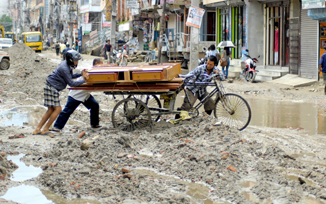 Passers-by helping a rickshaw-puller get the rickshaw out of a muddy road in Sinamangal, Kathmandu, on Thursday. The road section dug for expansion has not been repaired for months, and monsoon rains are giving  people a hard time. Photo: THT