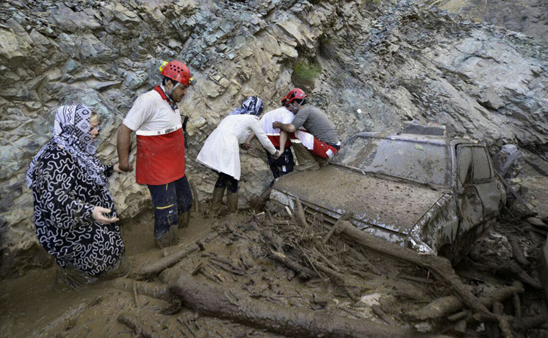 In this photo released by the Hamshahri Photo Agency on Monday, July 20, 2015, Iranian rescue crew members help people walk in a flooded road in Kan district, northern Tehran, Iran. Its state media said heavy rains triggered deadly flash floods in a mountainous area in the country's north. State TV said authorities fear more casualties from the Sunday evening floods in the provinces of Tehran, Alborz and Qazvin. It said a Chinese national was among those killed. Photo: AP