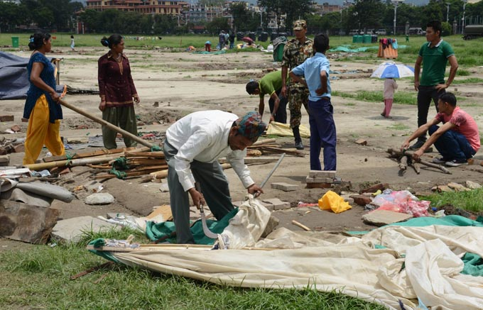 In this photograph taken on July 23, 2015, Rabi Baral (C) gathers his belongings to set up a new tent at a relief camp for earthquake survivors in Kathmandu. Photo: AFP
