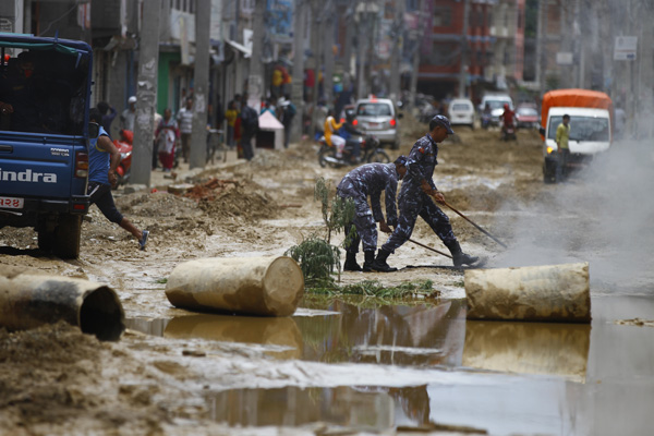 Security personnel douse a fire set by locals while staging a street protest, demanding immediate construction of the Old Baneshwor-Sinamangal road section, in Kathmandu, on Friday.  Locals complain that they have been facing a hard time, as the road section, dug about three years ago, is yet to be be constructed. Photo: THT