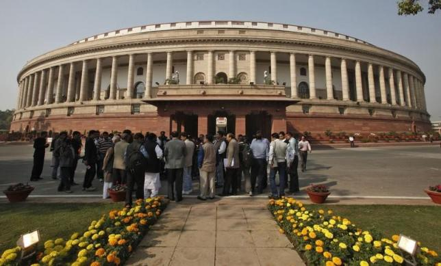 People stand in front of parliament building in New Delhi November 22, 2012. REUTERS/B Mathur/Files