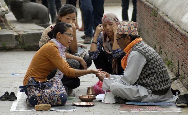 A woman showing her hand to a palmist , as her friends look on, on the premises of Pashupatinath Temple, in Gaushala, Kathmandu, on Saturday. Photo: Naresh Shrestha/THT