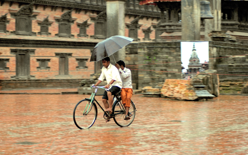 A pillion rider holds an umbrella as his friend pedals along during rainfall, in Bhaktapur of Nepal, in July 2015. Photo: THT