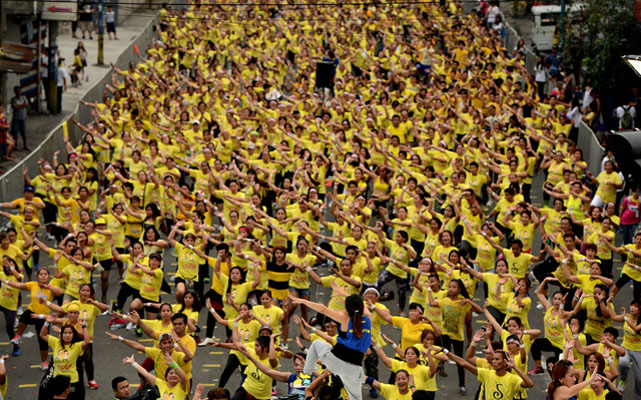 Filipino residents participate in a Zumba class in an attempt to break the Guinness World Record in Mandaluyong on July 19, 2015. Residents broke the record for the largest Zumba class with 12,975 participants in a single venue. Photo: AFP