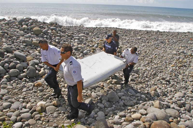In this photo dated Wednesday, July 29, 2015, French police officers carry a piece of debris from a plane in Saint-Andre, Reunion Island. Air safety investigators, one of them a Boeing investigator, have identified the component as a 'flaperon'; from the trailing edge of a Boeing 777 wing, a U.S. official said. Flight 370, which disappeared March 8, 2014, with 239 people on board, is the only 777 known to be missing. Photo: AP