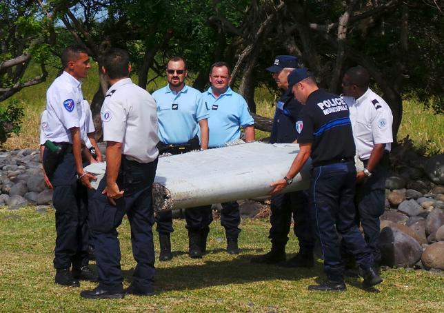 French gendarmes and police carry a large piece of plane debris which was found on the beach in Saint-Andre, on the French Indian Ocean island of La Reunion, July 29, 2015. REUTERS/Zinfos974/Prisca Bigot