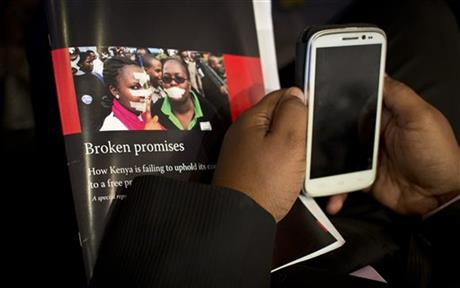 A journalist holds a copy of a report into the state of press freedom in Kenya, at a press conference to launch the report in Nairobi, Kenya Wednesday, July 15, 2015. Press freedom is deteriorating in Kenya as a result of government legislation, threats and attacks, the media rights group Committee to Protect Journalists (CPJ) said Wednesday. AP
