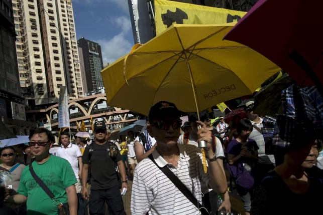 A pro-democracy protester holds a yellow umbrella, the symbol of the Occupy Central movement, during a march to demand universal suffrage in Hong Kong, China July 1, 2015. REUTERS/Tyrone Siu